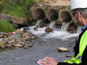 compliance inspection reveals rubbish along creek's edge near storm water outlet